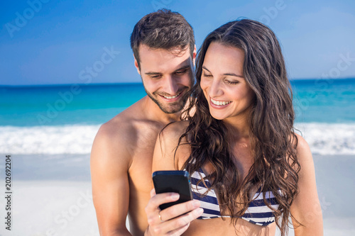 Happy couple using smartphone at the beach