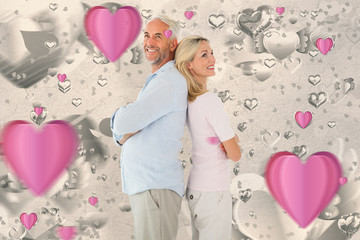 Smiling couple standing leaning backs together against grey valentines heart pattern