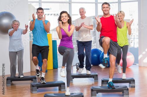People performing step aerobics exercise in gym © WavebreakmediaMicro