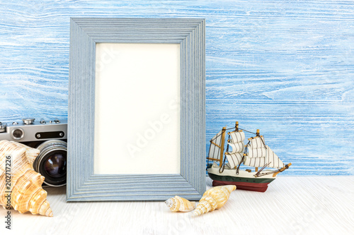 summer vacation background with old camera, photo frame, decorative ship and seashells