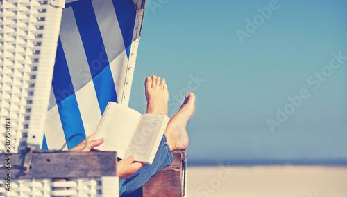 Leinwandbild Motiv Lesen im Strandkorb