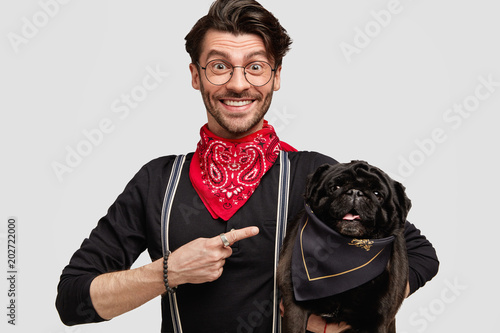 Look at my lovely pet! Positive stylish male model in elegant clothes, indicates at black pug dog with elegant bandana, happy to have walk together, isolated on white background. People and animals