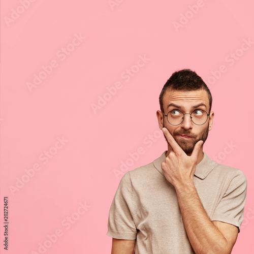Vertical shot of pensive bearded young male holds chin and contemplates about something, wears round spectacles and t shirt, poses against pink background with copy space for your advertisement © Wayhome Studio