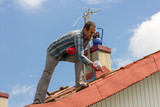 roofer paints the roof - 202732000