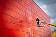Leinwanddruck Bild - worker of Professional Facade Cleaning Services washing the red wall. Worker wearing safety harness washes wall facade at height on modern building in a crane.