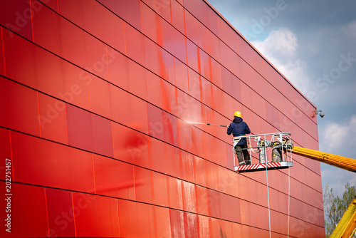 Leinwanddruck Bild worker of Professional Facade Cleaning Services washing the red wall. Worker wearing safety harness washes wall facade at height on modern building in a crane.