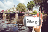 Hand holding smartphone showing against canal in amsterdam - 202762077
