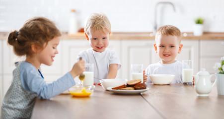 happy funny children eating breakfast