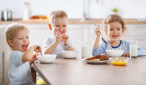 Wall mural happy funny children eating breakfast