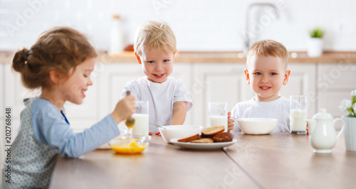 happy funny children eating breakfast