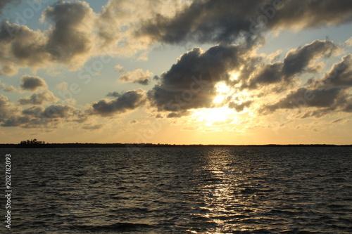 Plexiglas Zwavel geel Sun glowing from behind floating clouds over the water