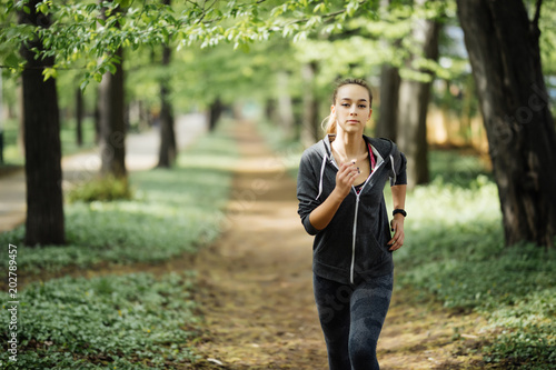 Fototapeta Young smiling sporty woman running in park in the morning. Fitness girl jogging in park