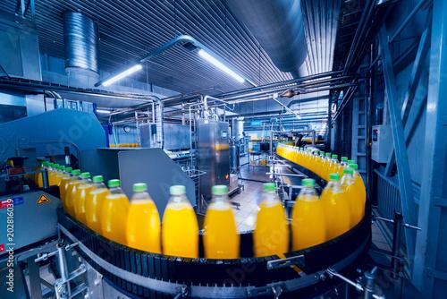 Leinwanddruck Bild Beverage factory interior. Conveyor with bottles for juice or water. Equipments