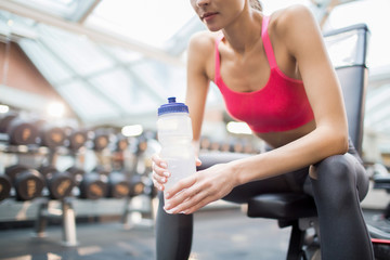 Young active woman with plastic bottle of water relaxing between trainings in fitness center © pressmaster