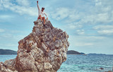 Happy tourist sits on a big rocky stalactite reef on the shore of the ocean. Philippine Islands. Pacific ocean.