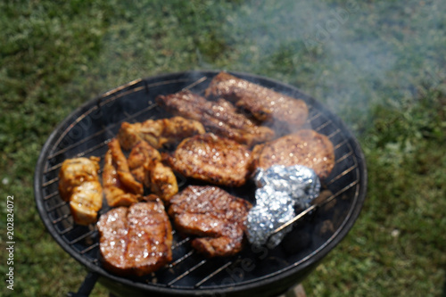 small round grill with pork and chicken and potato in aluminum foil over green grass in the garden