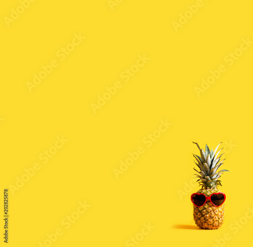Pineapple wearing sunglasses on a yellow background - 202825878