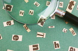letters cut from newspaper and magnifying glass on green background