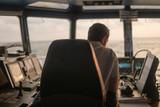 Deck navigation officer on the navigation bridge. He looks at radar screen. Watchkeeping, collision prevention at sea. COLREG