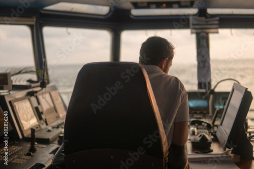 Poster Deck navigation officer on the navigation bridge. He looks at radar screen. Watchkeeping, collision prevention at sea. COLREG