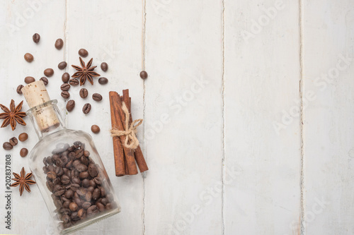 Plexiglas Koffiebonen Grains of coffee in a glass jar, with cinnamon and badan, on a light wooden texture. With empty space for writing