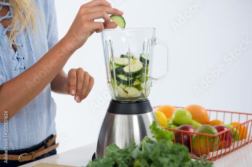 Woman preparing vegetable smoothie
