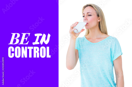 Leinwandbild Motiv Pretty blonde drinking glass of water against purple vignette