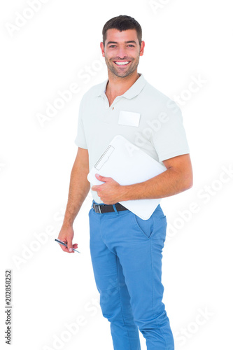 Smiling male handyman with clipboard and pen on white background
