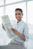 Gleeful chic businesswoman holding newspaper smiling at camera - 202861011