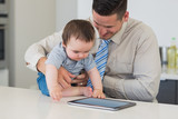 Businessman holding baby using tablet computer - 202865403