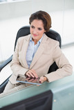Thinking businesswoman holding tablet - 202872472