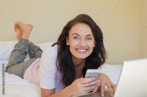 Beautiful woman text messaging in bed