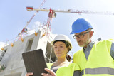 Construction manager and engineer working on building site - 202876664