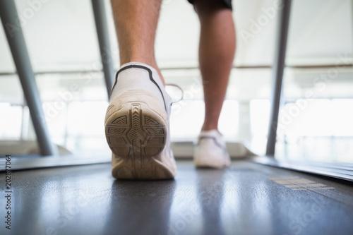 Wall mural Man walking on the treadmill