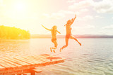 Fototapety Two girls in bathing suits jumping from a wooden pier into the water against a background of blue mountains in the sunlight