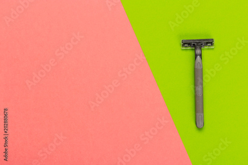 Disposable razor on a bright bicolored background, top view
