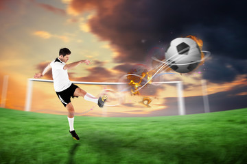 Football player in white kicking against football pitch under cloudy orange sky