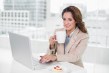 Cheerful businesswoman using laptop at her desk and holding mug - 202883856