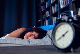 Photo of brunette with insomnia lying on bed next to alarm clock at night