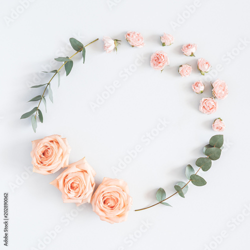 Flowers composition. Wreath made of rose flowers, eucalyptus branches on pastel gray background. Flat lay, top view, copy space, square © Flaffy