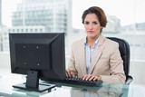 Stern businesswoman sitting looking at camera - 202905470
