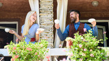 Neighbours drinks coffee at balcony and speaking. - 202907844