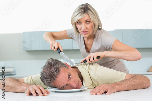 Angry woman holding knife to mans neck in kitchen