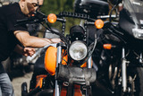 Adult and experienced biker cleaning and washing his motorcycle - 202924635