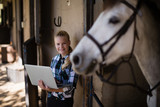 Teenage girl using laptop in the stable - 202928286