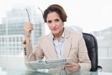 Focused businesswoman holding newspaper - 202935237