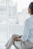 Chic dark haired businesswoman sitting in her office - 202946287