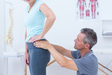 Physiotherapist examining his patient back  - 202947630