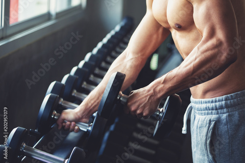 Fototapeta Fitness man doing exercise in gym