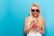 Happy young woman drinking smoothie on a blue background